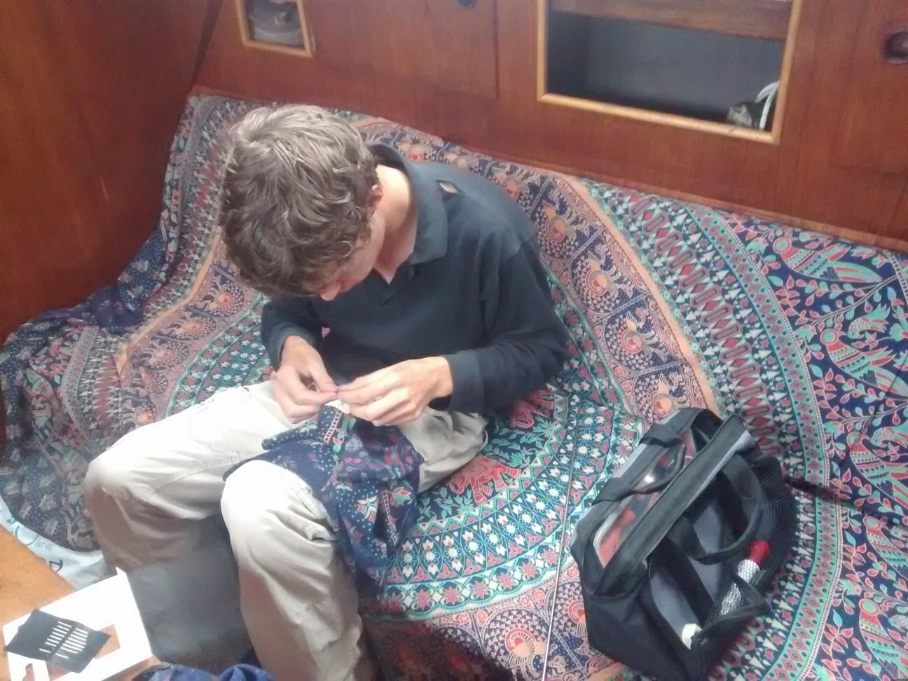 Félicien essaye de coudre malgré les nœuds dans le fil .